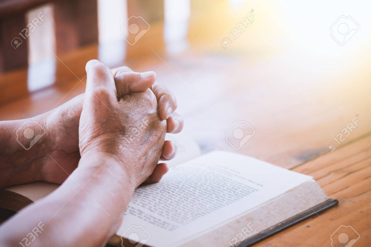 Elder woman hands folded in prayer on a Holy Bible for faith