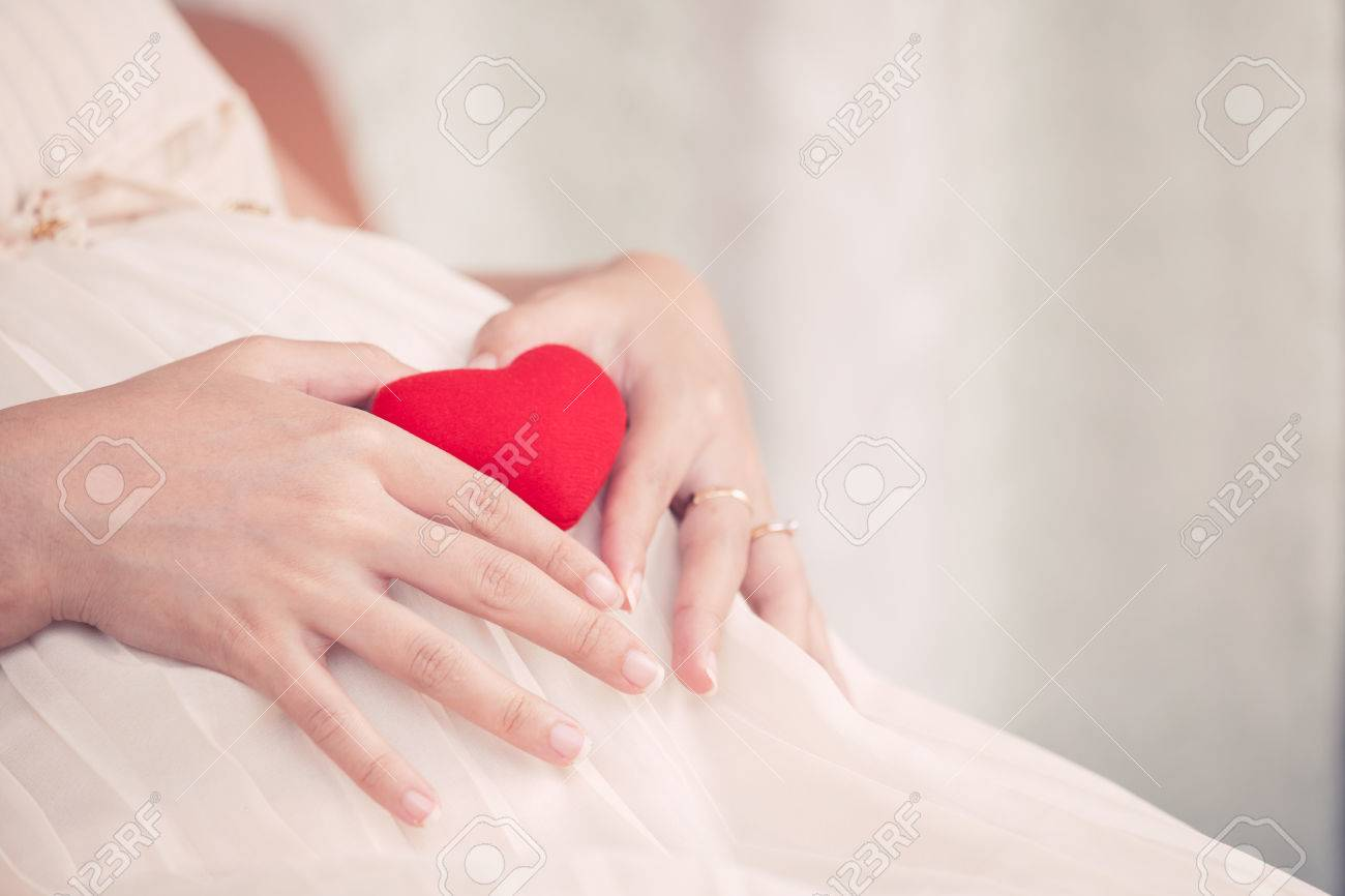 Pregnant Woman Sitting And Making Hand Heart Shape With Red Heart ...