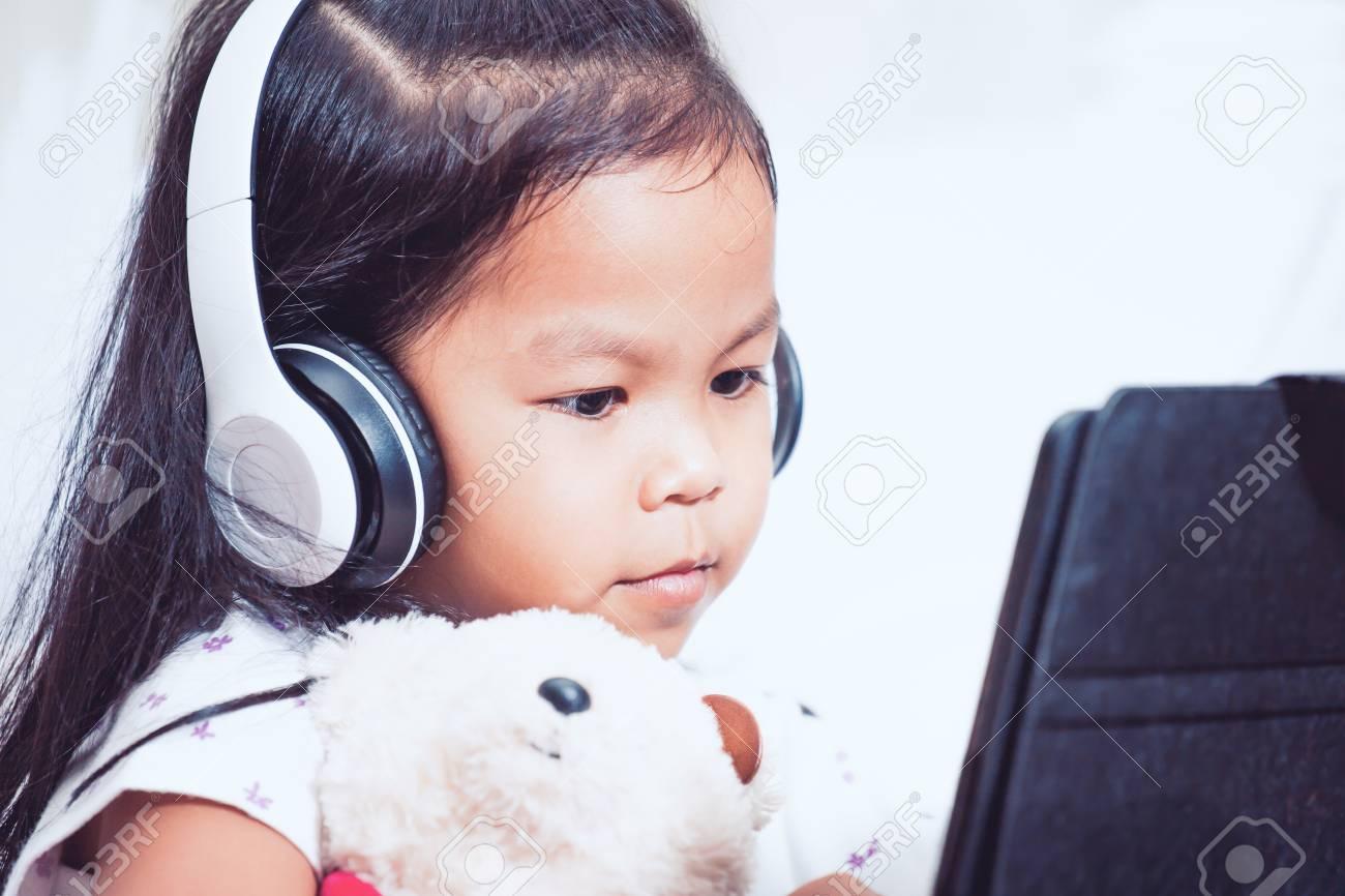 Mignonne petite fille enfant asiatique dans les écouteurs utilise une  tablette dans sa chambre dans le ton de couleur vintage