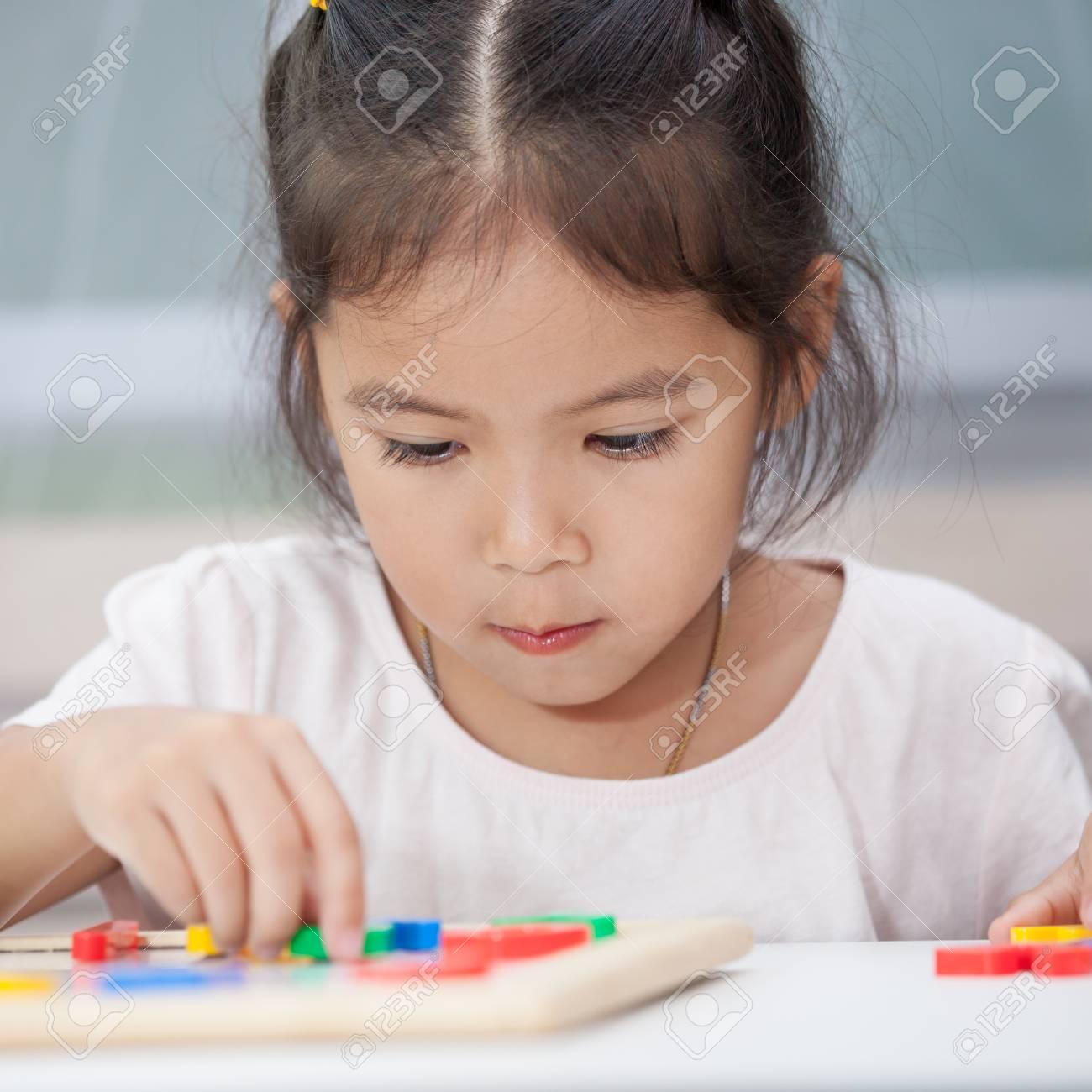 e80fb092e14 Foto de archivo - Niña linda que se divierte jugando y aprendiendo  alfabetos magnéticos a bordo en la habitación.