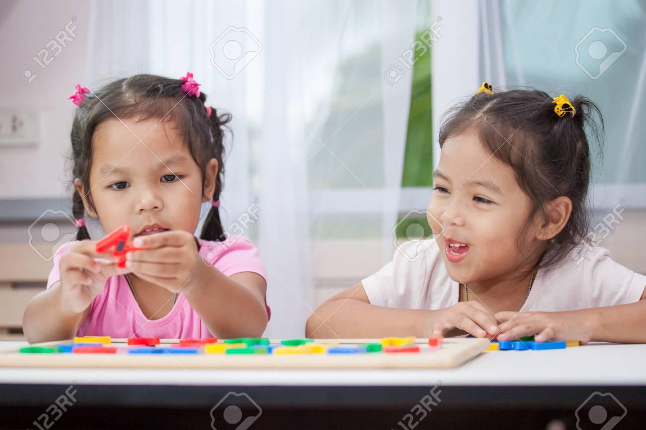 6c6284f1d65 Dos muchachas asiáticas lindas del niño que se divierten para jugar y  aprender alfabetos magnéticos juntos