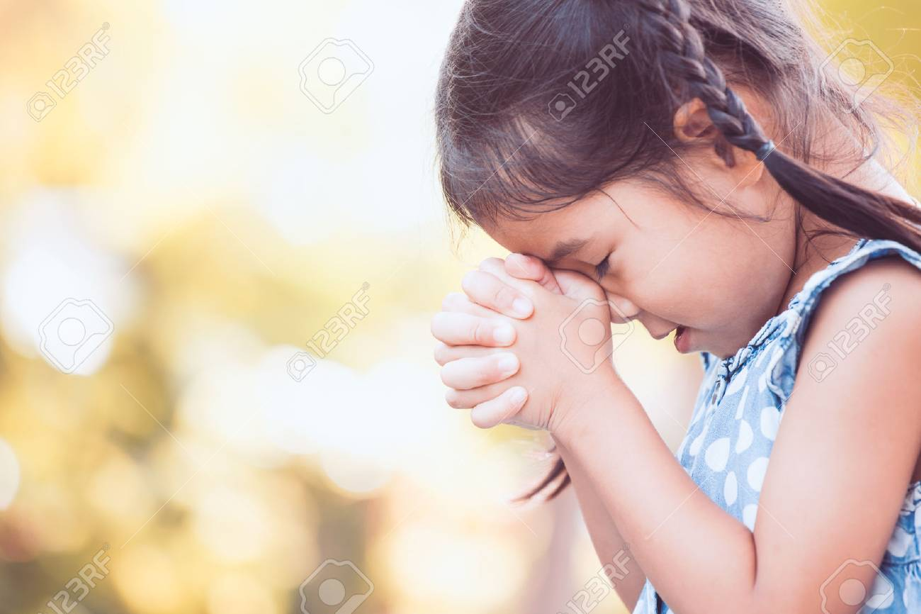 Cute Asian Little Child Girl Praying With Folded Her Hand For