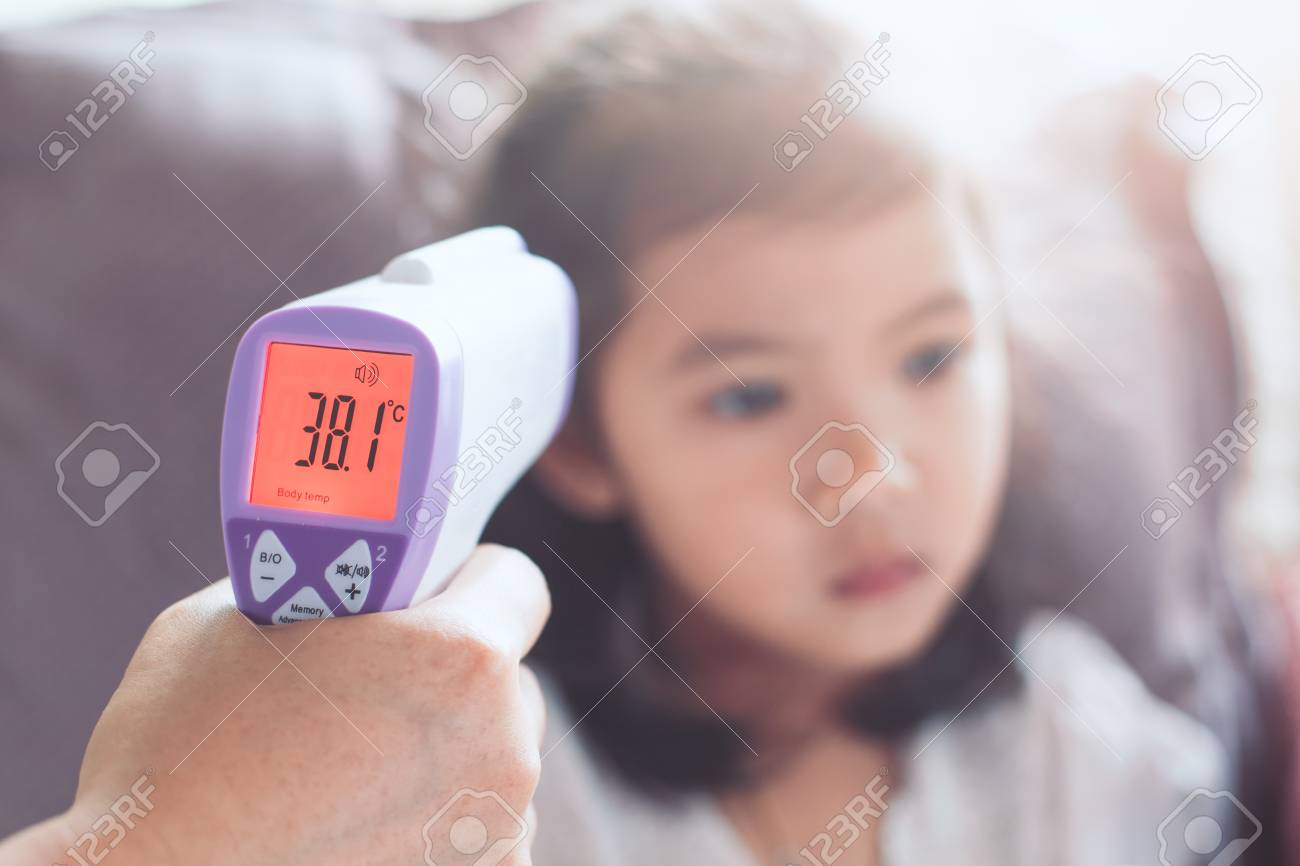 Mother measuring temperature her sick asian little child girl with infrared thermometer - 91268954