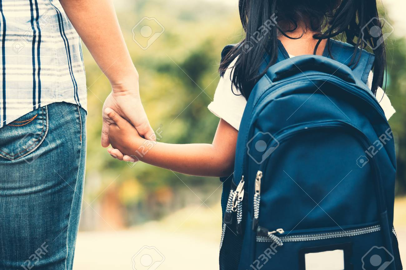 Back to school. Cute asian pupil girl with backpack holding her mother hand and going to school in vintage color tone - 106242123