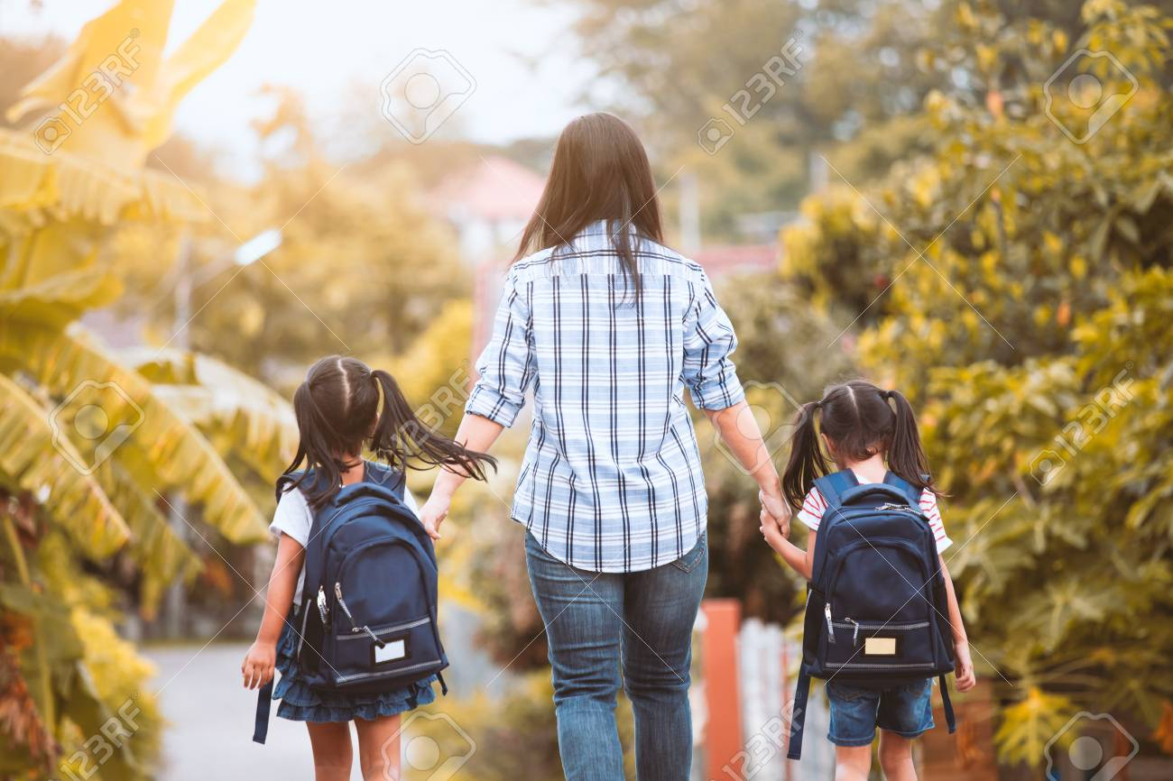 Back to school. Asian mother and daughter pupil girl with backpack holding hand and going to school together in vintage color tone - 107101172