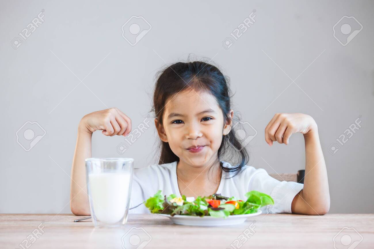 Cute asian child girl eating healthy vegetables and milk for her meal - 126866450