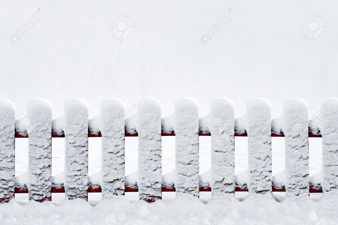 Sparse composition with red wooden fence covered in snow Stock Photo - 16651856