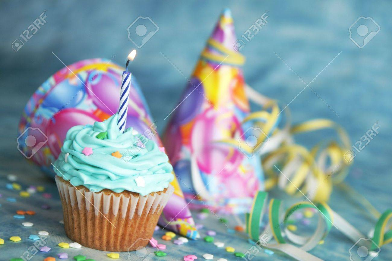 Blue Birthday Cake With Candle On Top And Hat Twinkel In The Background Stock Photo