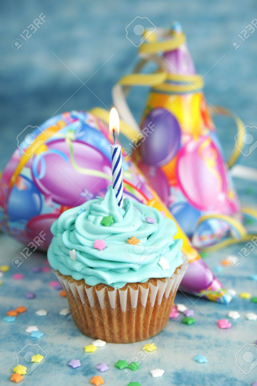 Blue Birthday Cake With Candle On Top And Hat In The Background Stock Photo