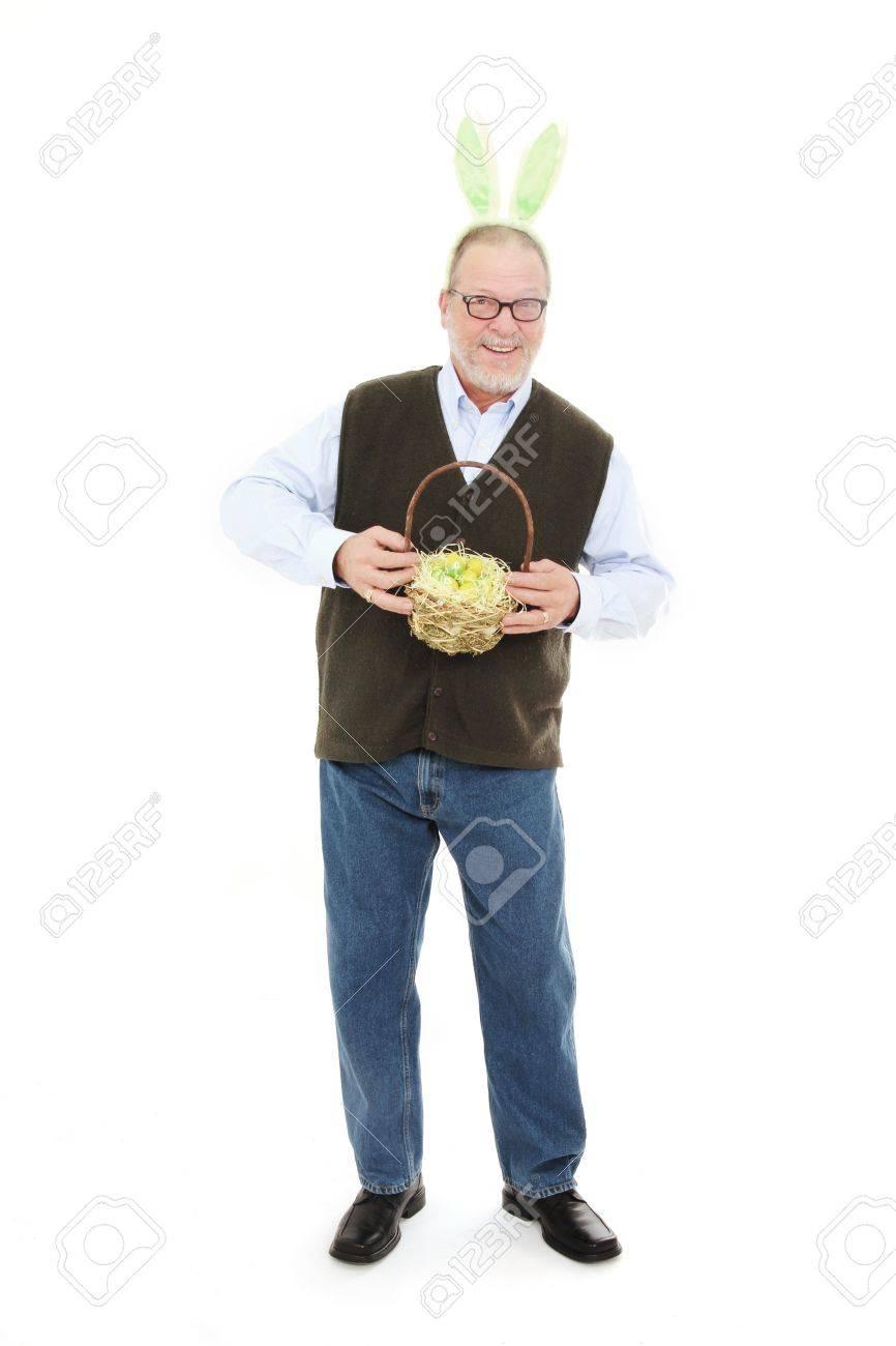 Happy senior man with green rabbit ears holding a easter basket happy senior man with green rabbit ears holding a easter basket full of yellow eggs stock negle Gallery