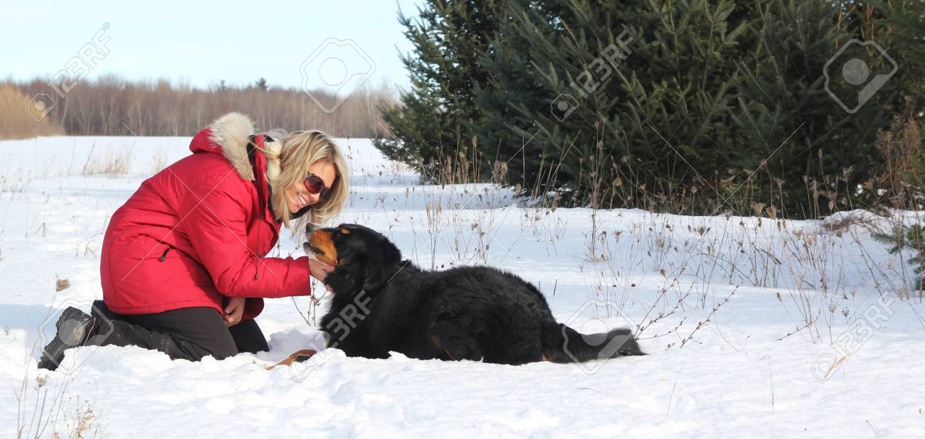 Woman with red jacket laying in snow with her dog Stock Photo - 12578948
