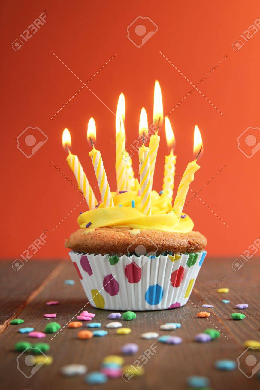 Cupcake with yellow icing full of yellow candles on orange background Stock Photo - 13966996