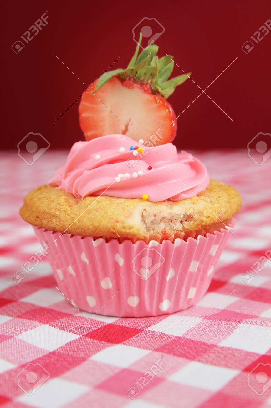 Pink cupcake with a bith taken on a pink checkerd tablecloth Stock Photo - 13985209