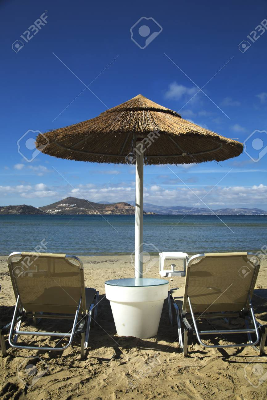 Sunbathing Chairs And Straw Umbrella On St Georges Beach In Naxos, Greece  Stock Photo