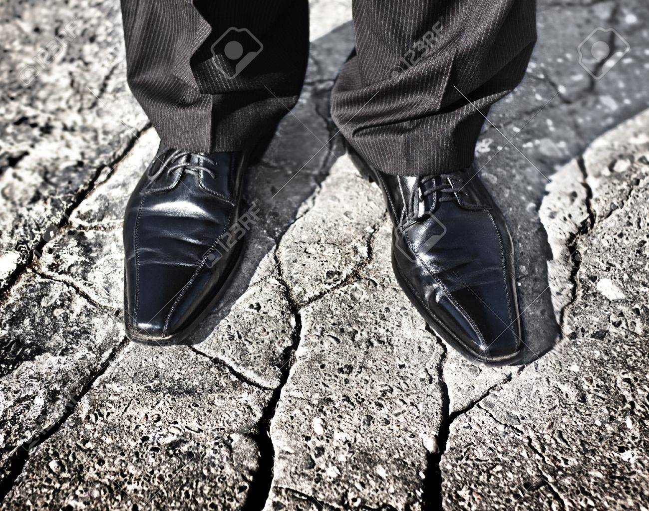 Businessman legs standing on a cracked ground - uncertain future, insecure situation or risky investment decision concept Stock Photo - 18660766