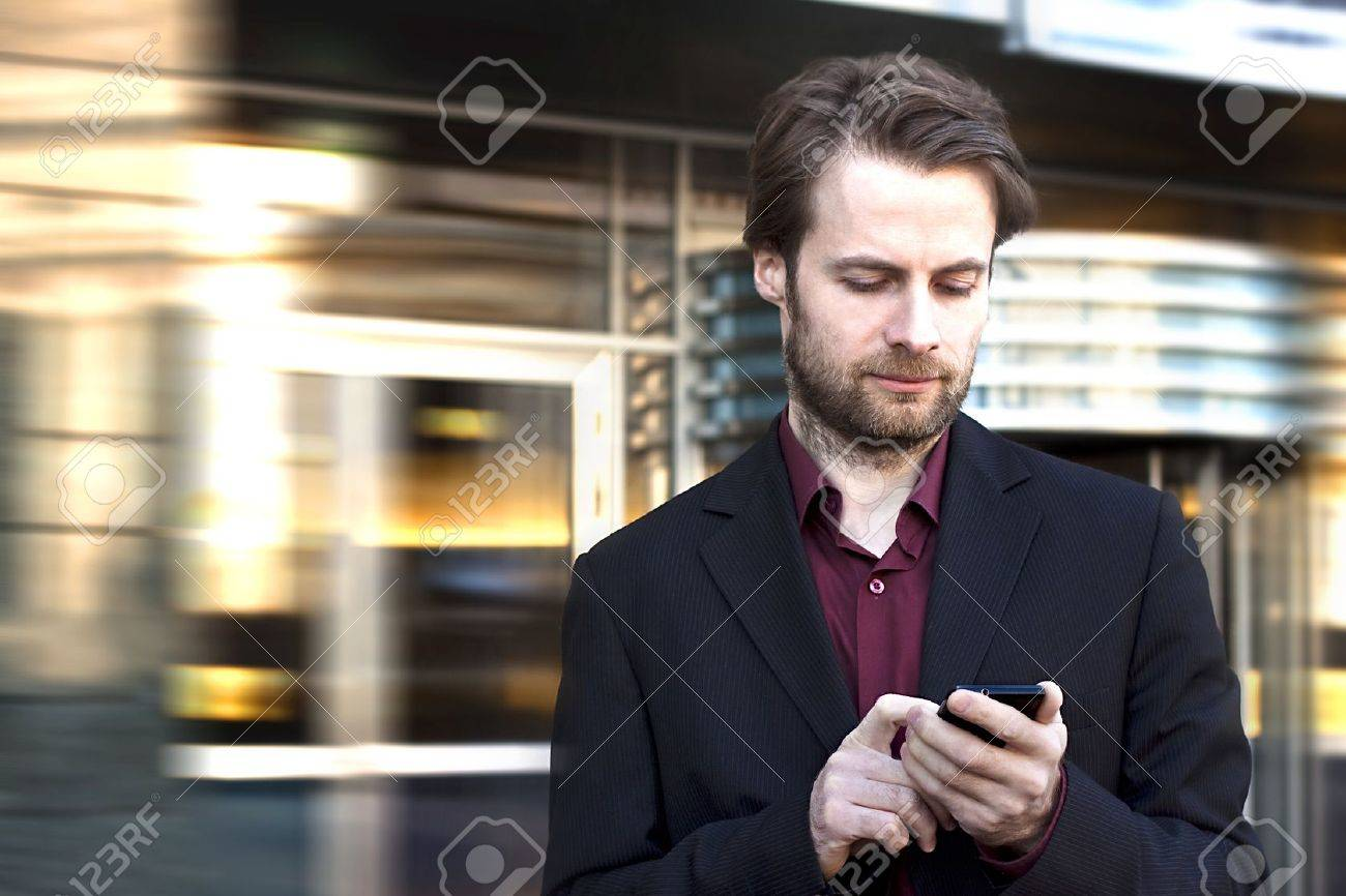 Forty years old businessman standing outside modern office building looking on a mobile phone Stock Photo - 18660758
