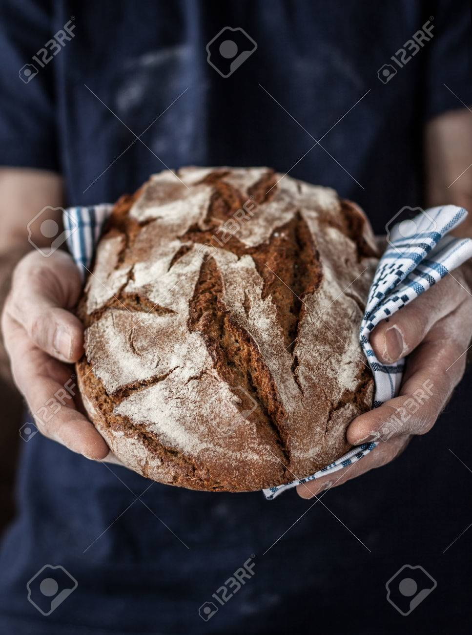 Baker man holding rustic organic loaf of bread in hands - rural bakery. Natural light, moody background with free text space good for poster or cover. - 55317387