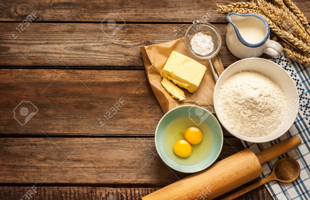 Baking cake in rural kitchen - dough recipe ingredients (eggs, flour, milk, butter, sugar) and rolling pin on vintage wood table from above. - 55317487