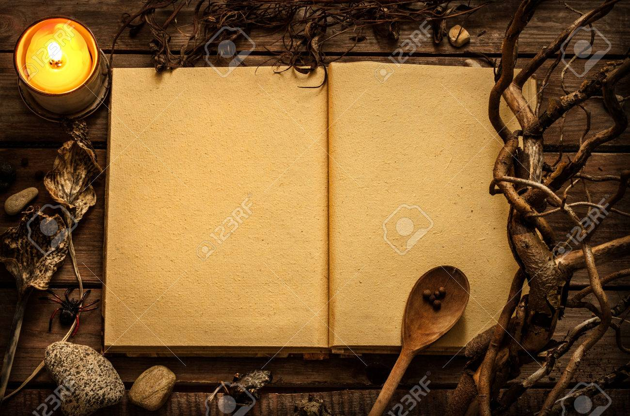 Old blank open witchcraft or magic recipes book with candle and alchemy ingredients around. Dark mysterious rustic background with text space. - 55317500