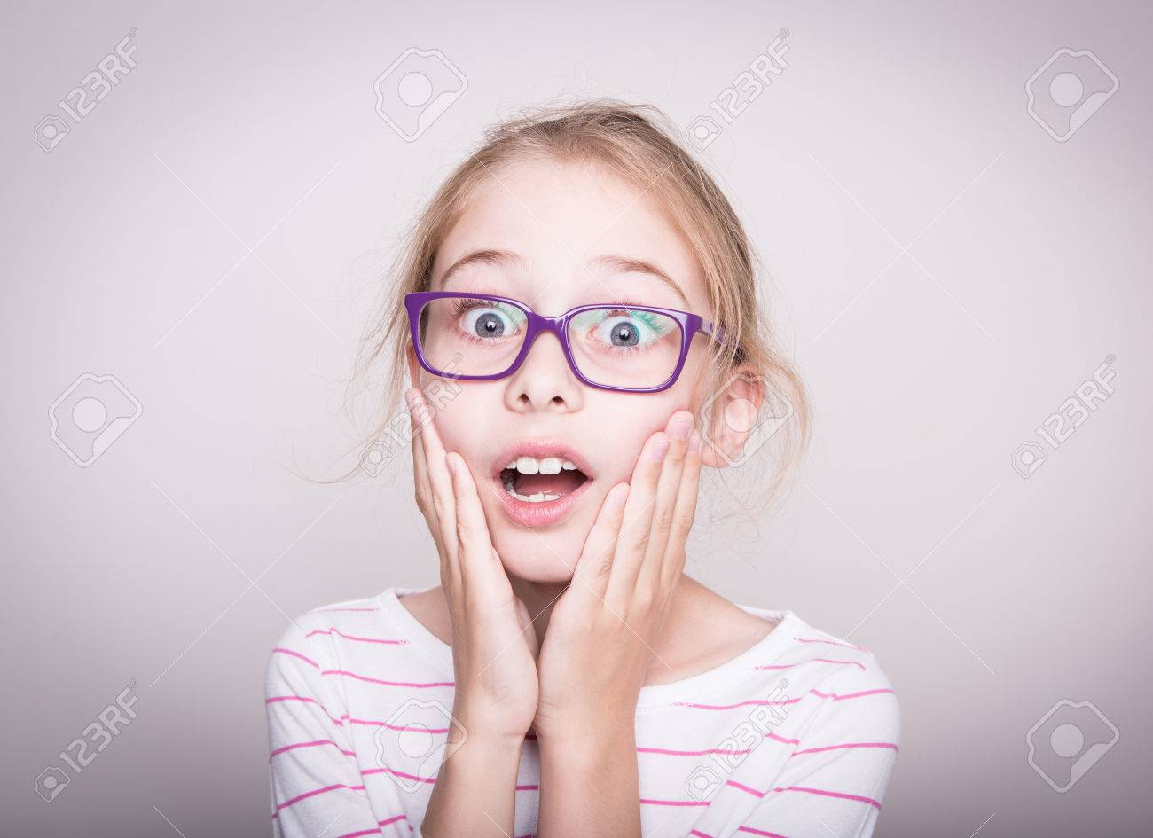Surprised or shocked face of eight years old pretty blond caucasian child girl in violet glasses. Shock - facial expression. Layout with free copy space. - 61728559