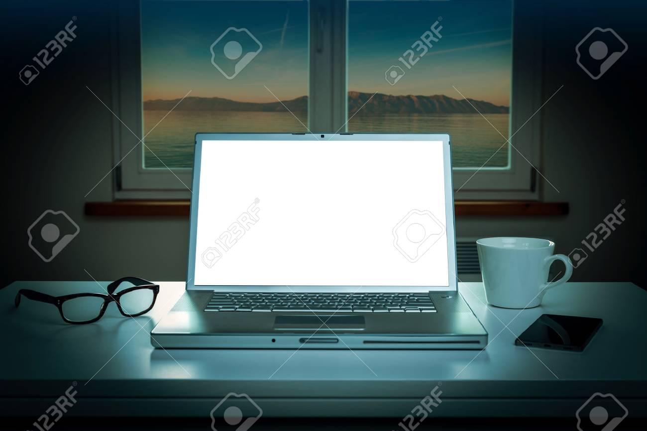 ordinateur portable avec écran blanc sur la table - paysage de nuit