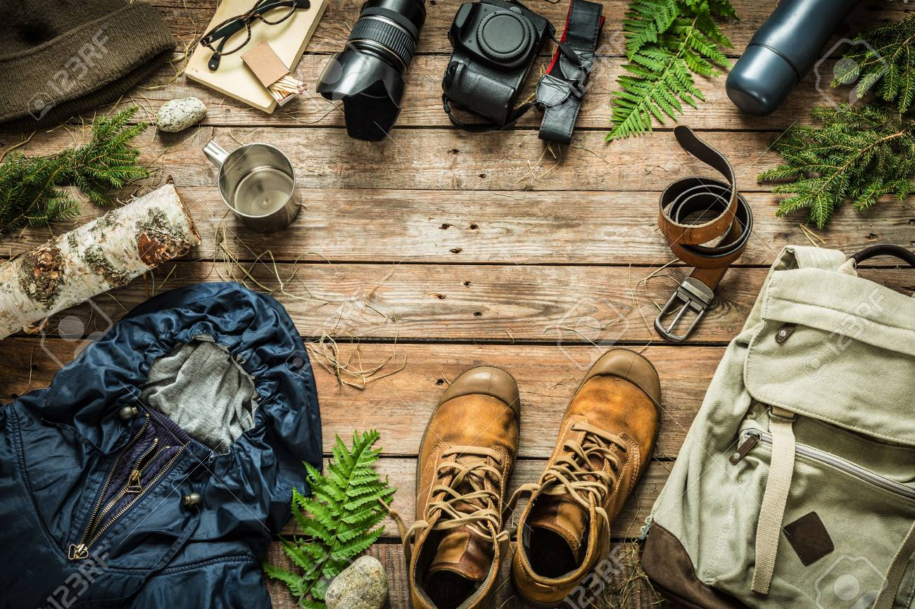 Camping or adventure trip scenery concept. Backpack, jacket, boots, belt, camera on wooden background captured from above (flat lay). Layout with free text (copy) space. - 86944926
