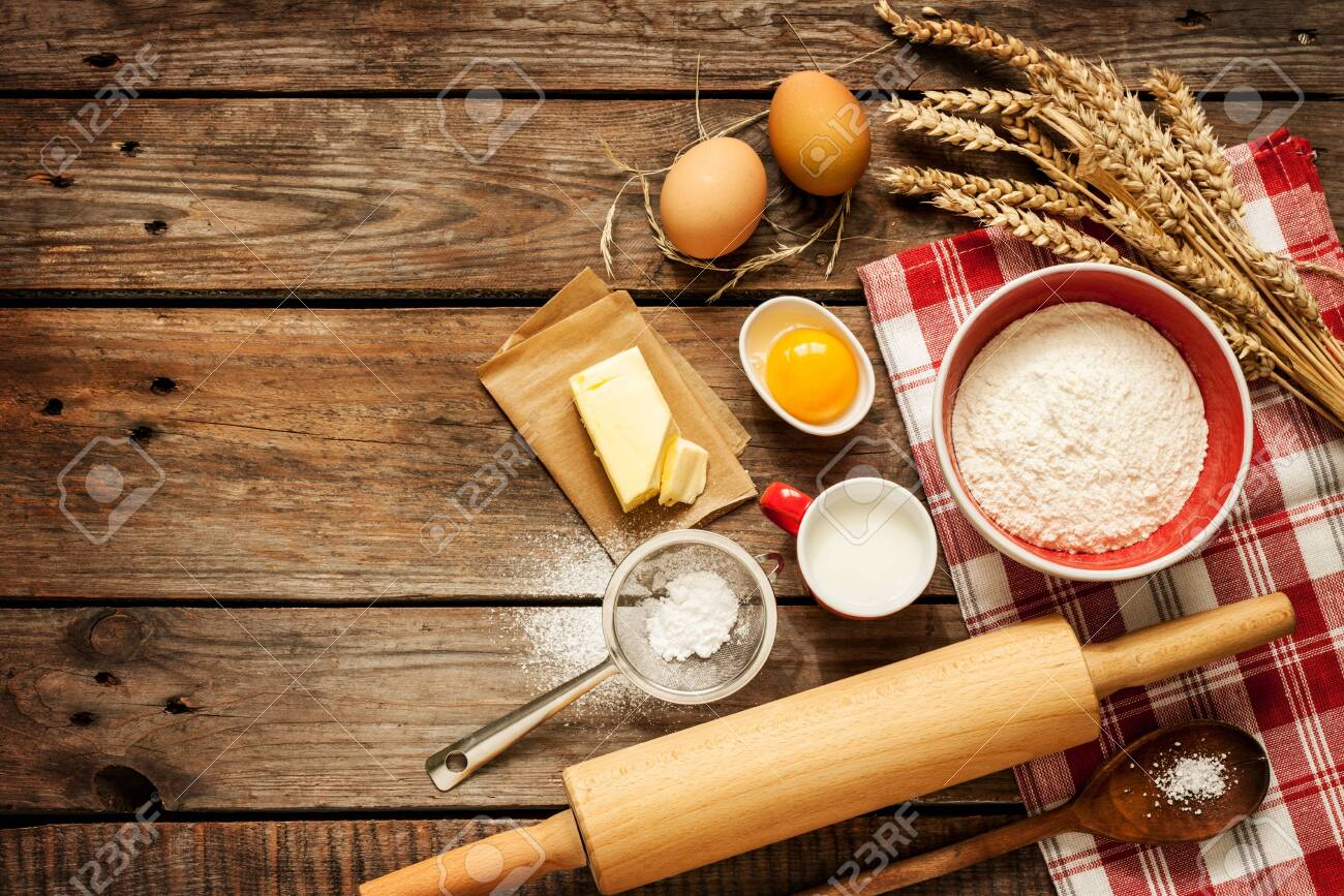 Baking cake in rural kitchen - dough recipe ingredients (eggs, flour, milk, butter, sugar) on vintage wooden table from above. Background layout with free text space. - 143533626