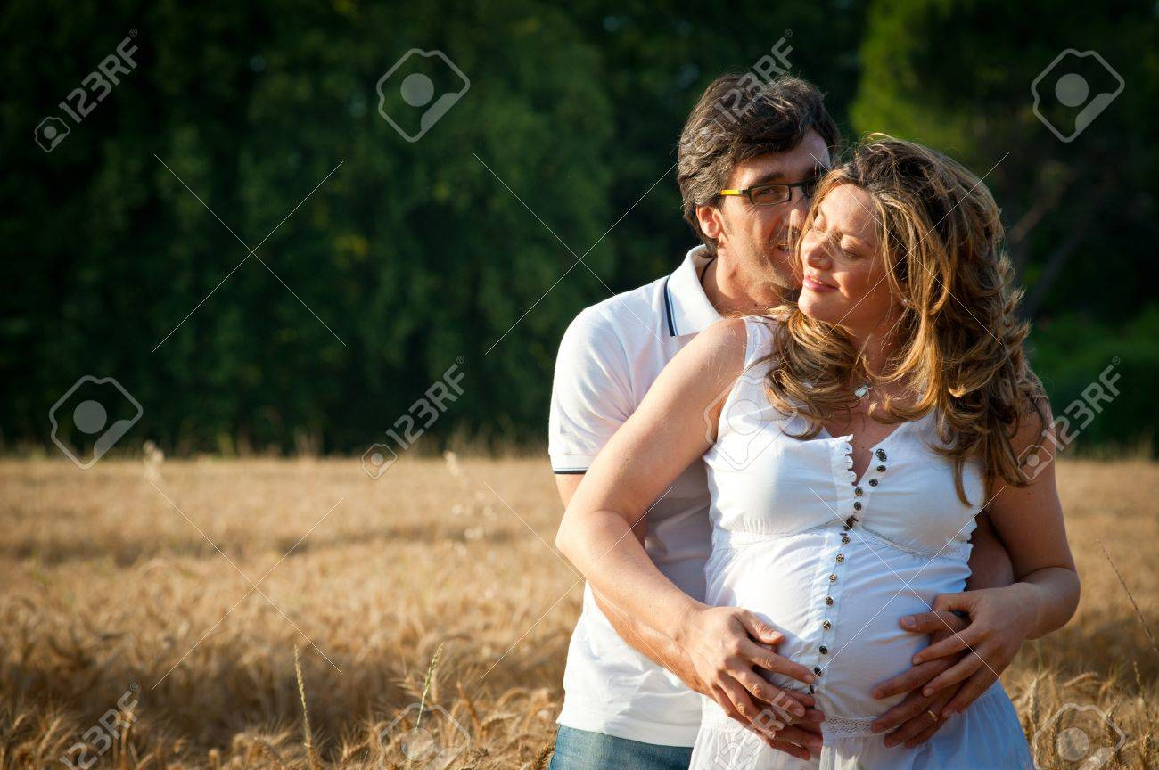 Husband embracing pregnant wife in a wheat field Stock Photo - 17505747