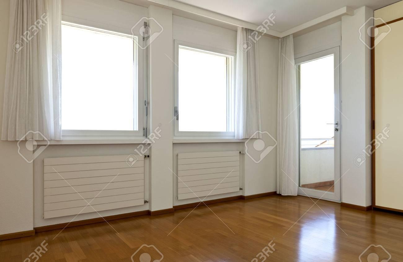 Interior de la casa, cuarto vacío, ventana con cortinas blancas