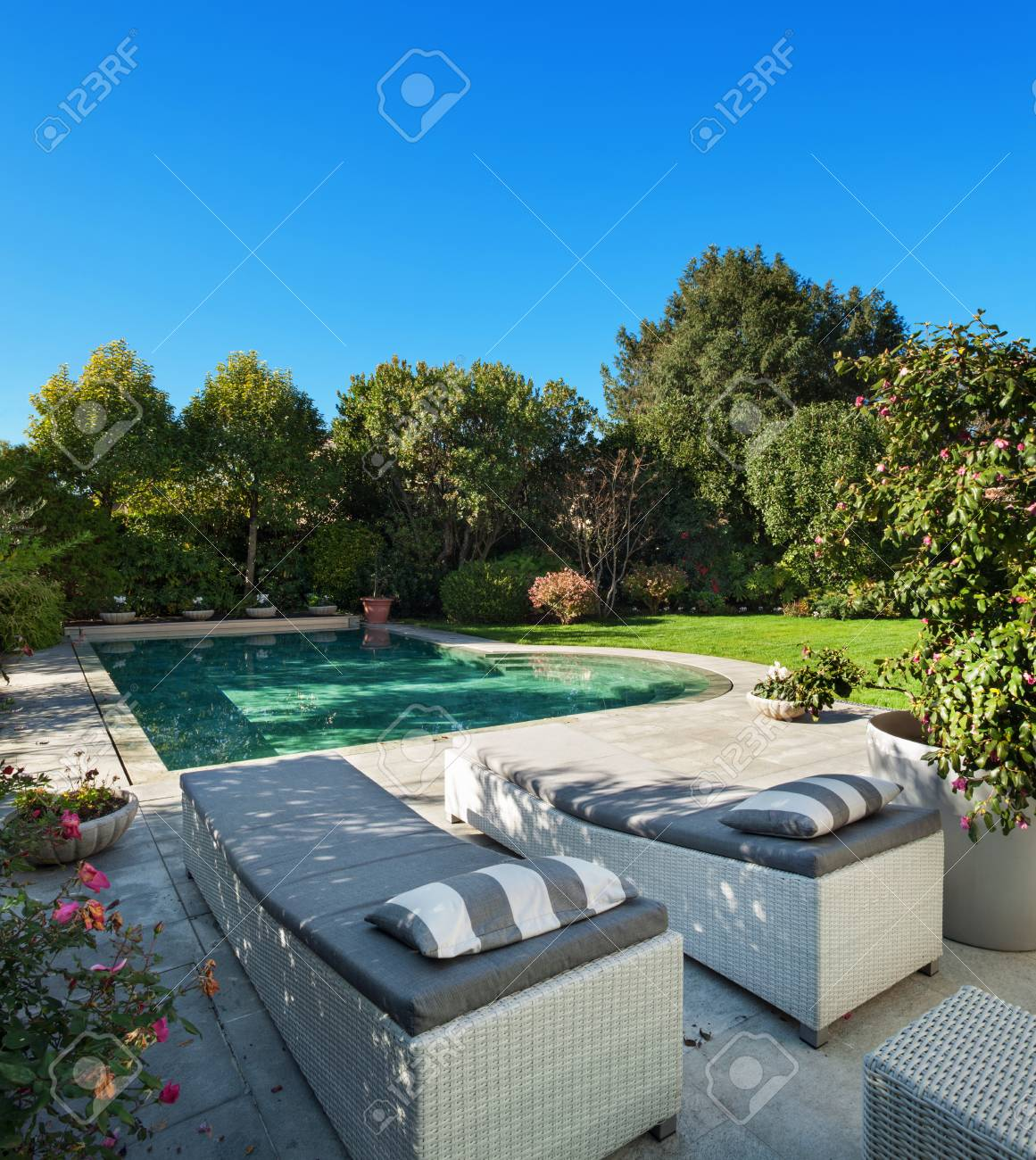 Schöner Garten Mit Pool, Zwei Sonnenliegen Standard Bild   53298801