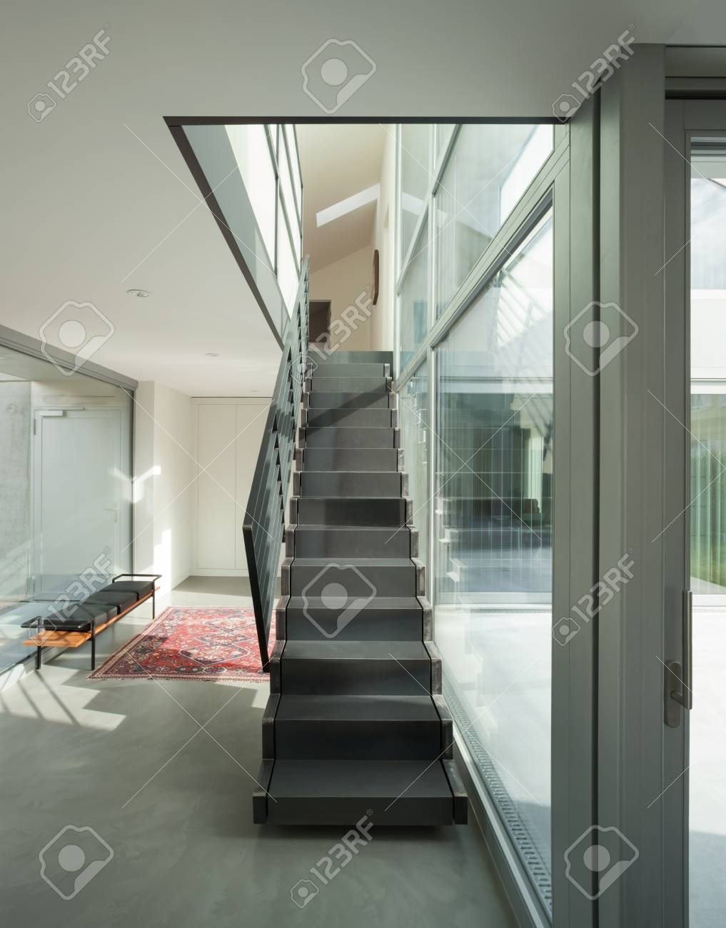 Interior of a modern house, hall with iron staircase
