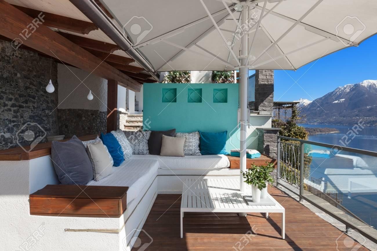Salón De La Terraza Con Cómodos Divanes Y Vista Al Lago En Una Casa De Lujo