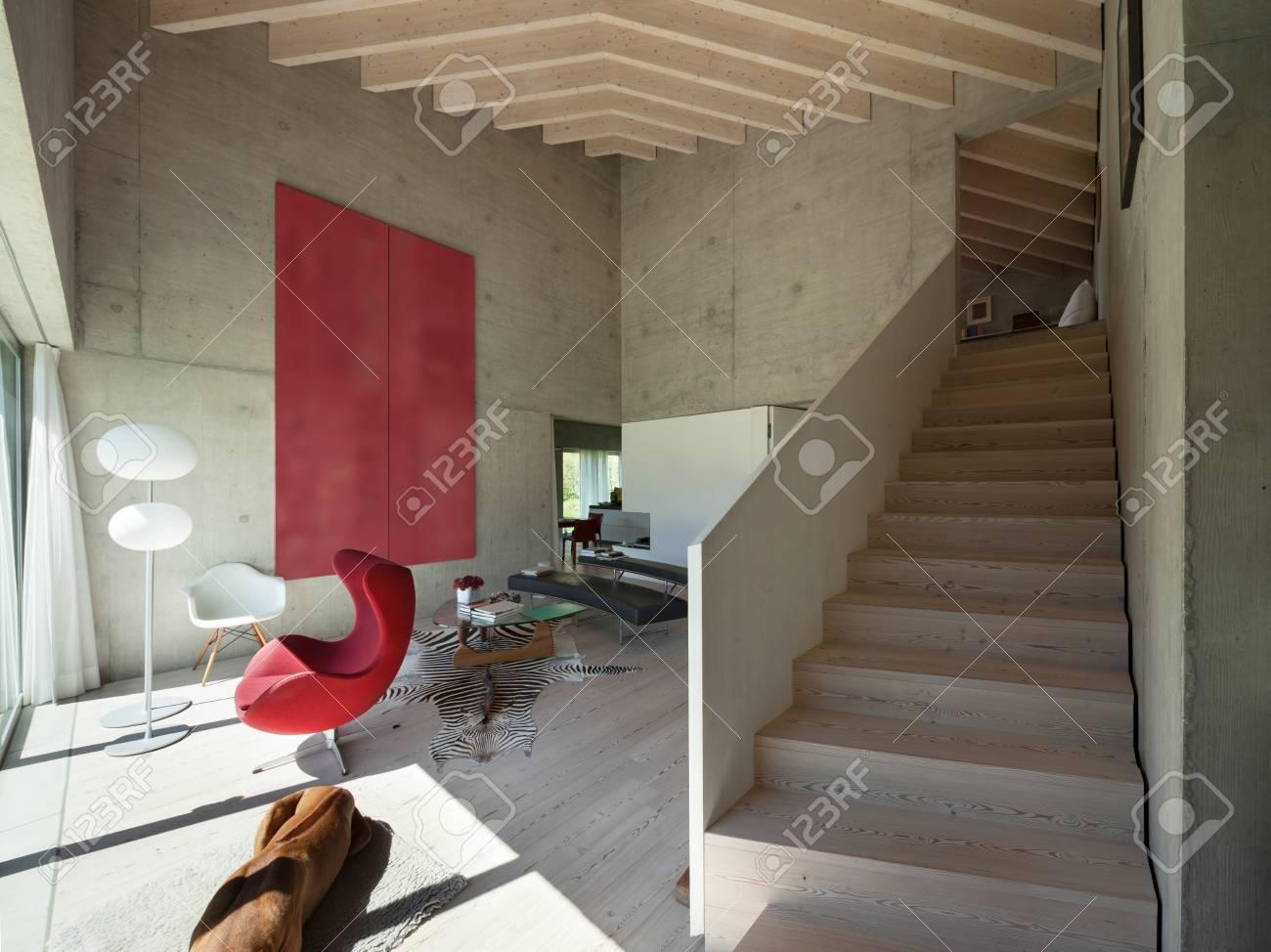 Intérieur d\'une villa, salon moderne avec un fauteuil rouge, des murs en  béton