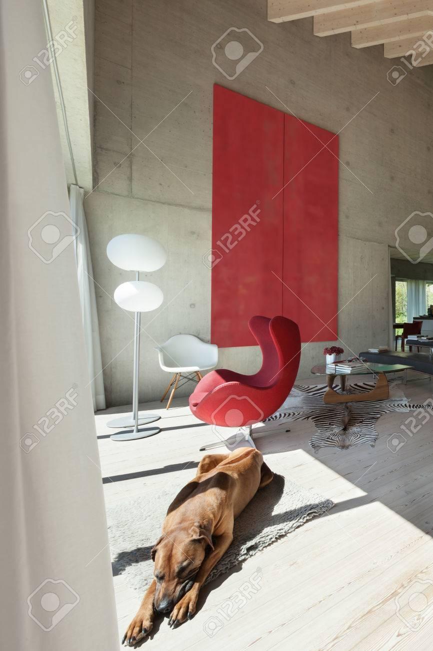 Intérieur d\'un loft, salon moderne avec un fauteuil rouge, des murs en béton