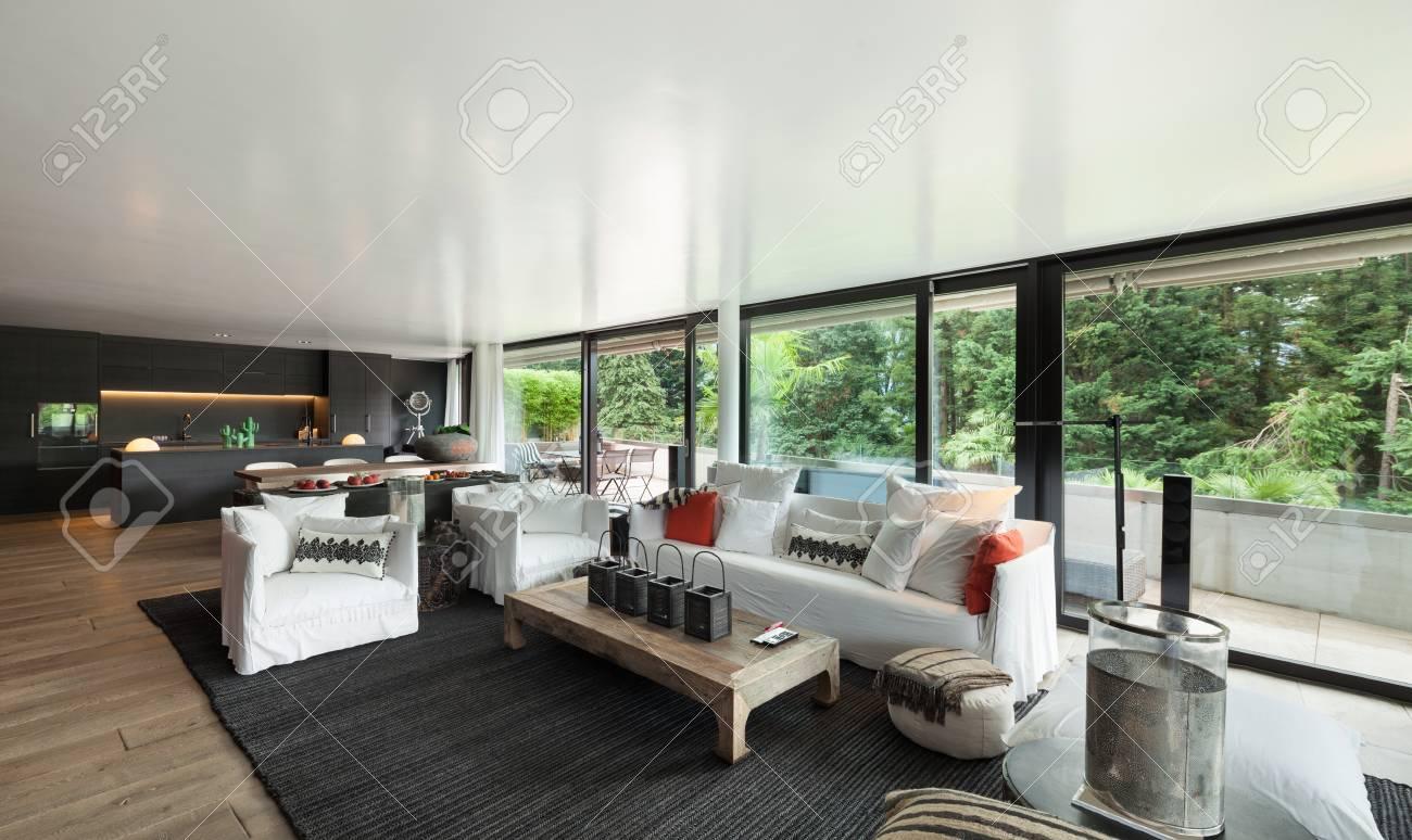 Soggiorno moderno con divani bianchi e grandi finestre