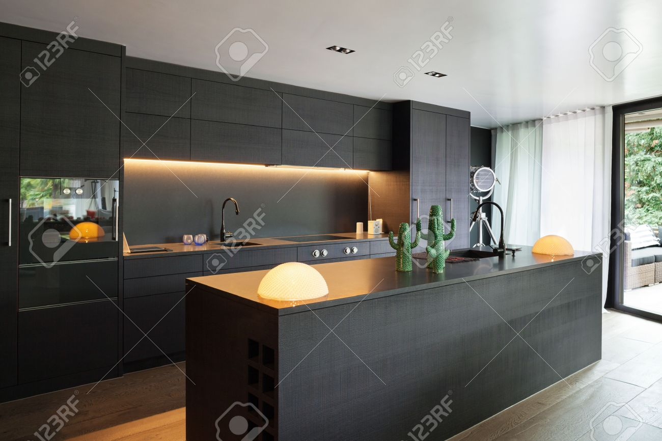 Modern kitchen with black furniture and wooden floor Archivio Fotografico - 61345144