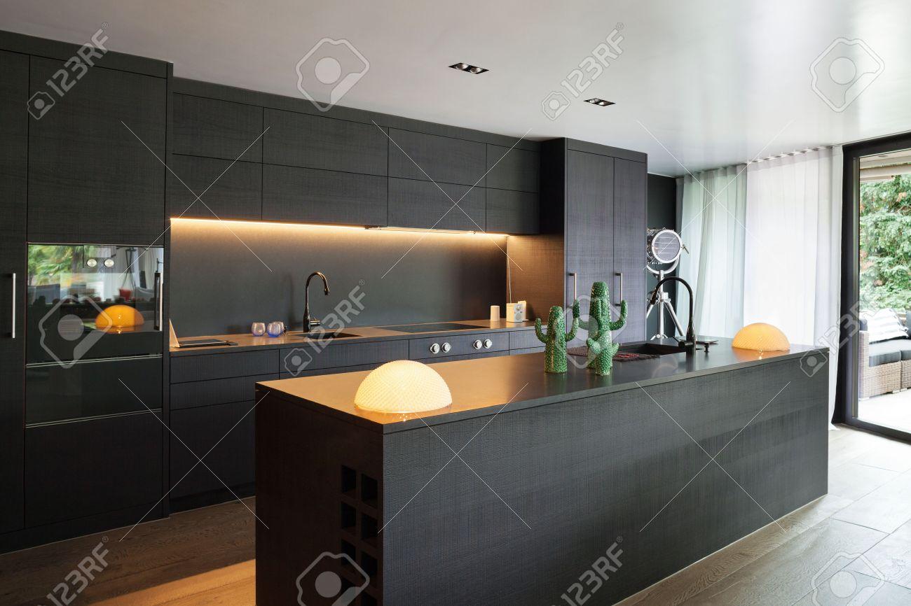 Moderne Küche Mit Schwarzen Möbeln Und Holzboden Standard Bild   61345144