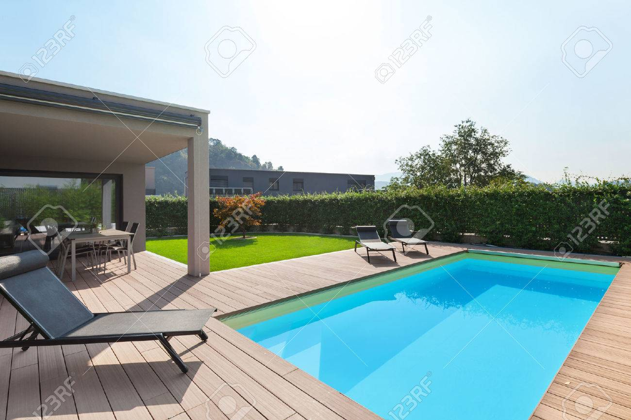 modern house with pool, loungers sun by the pool Archivio Fotografico - 64614067