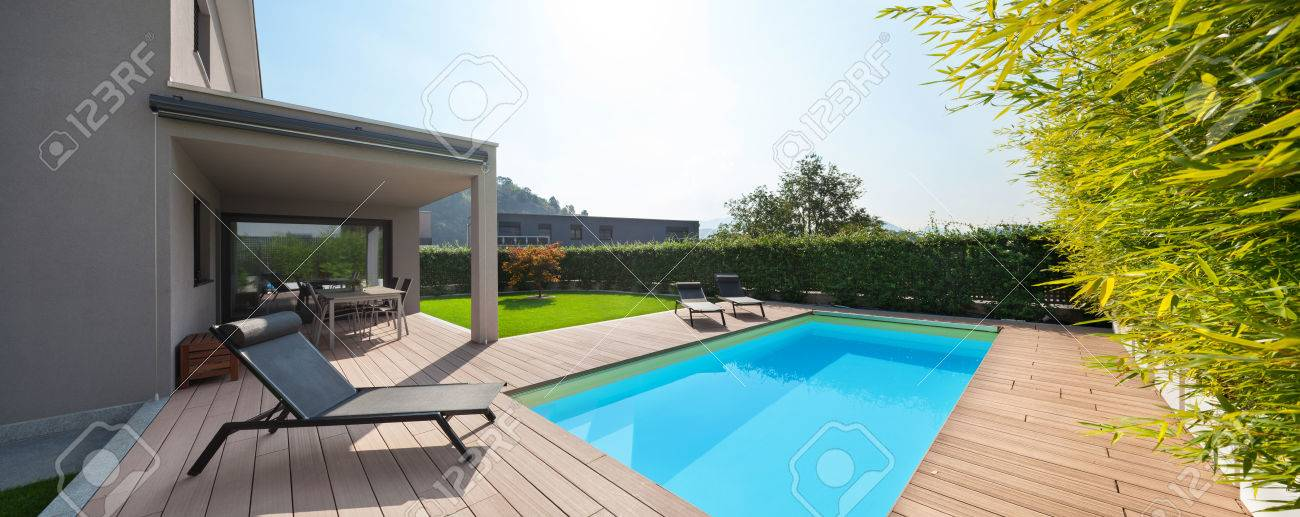 modern house with pool, loungers by the pool Archivio Fotografico - 64614080