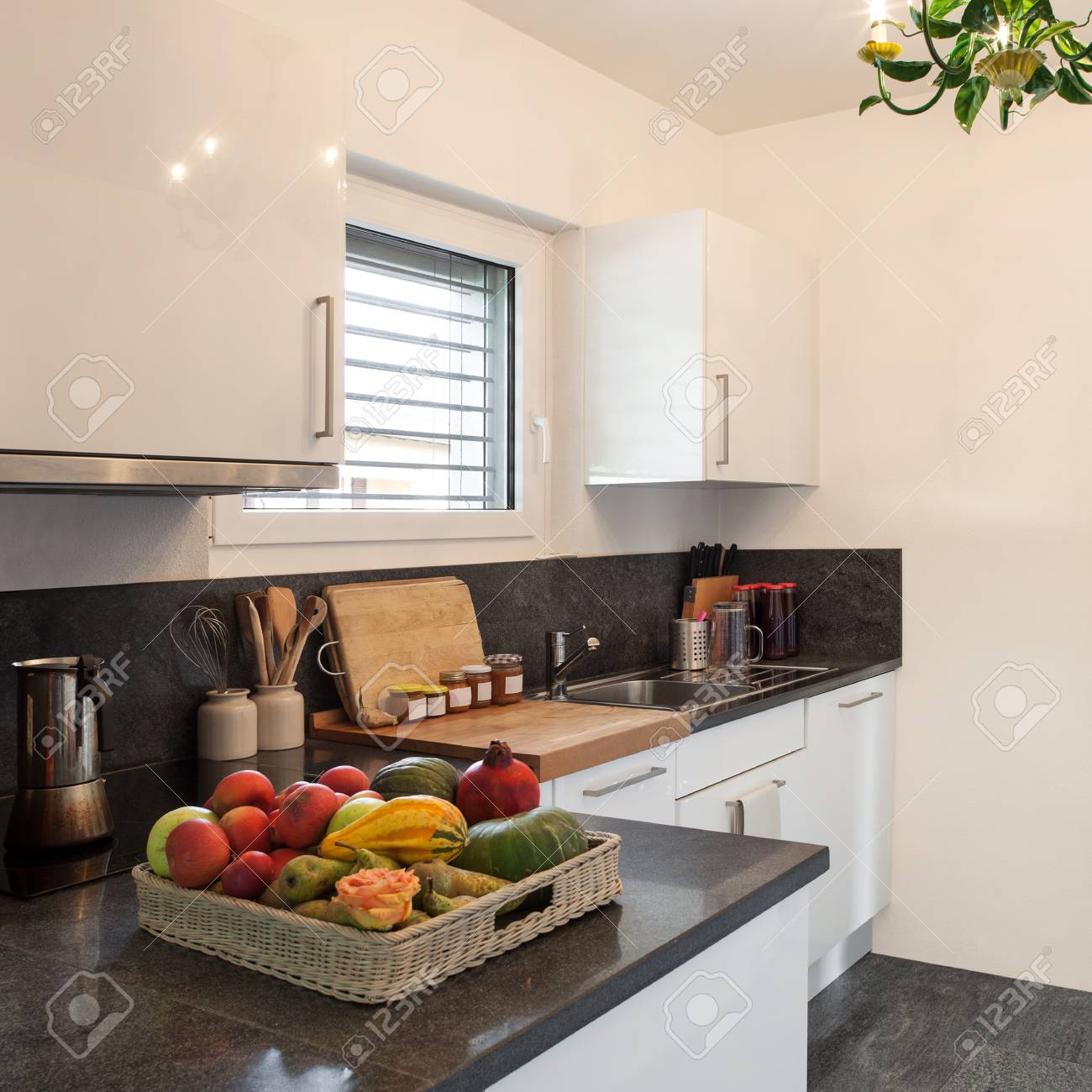Nice domestic kitchen of a home, fruit basket in the foreground