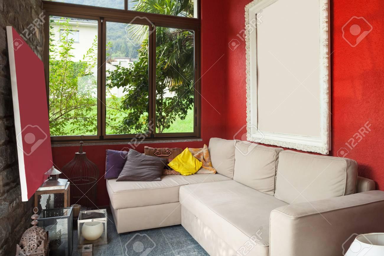 Interieur veranda met comfortabele divan rode muur royalty vrije