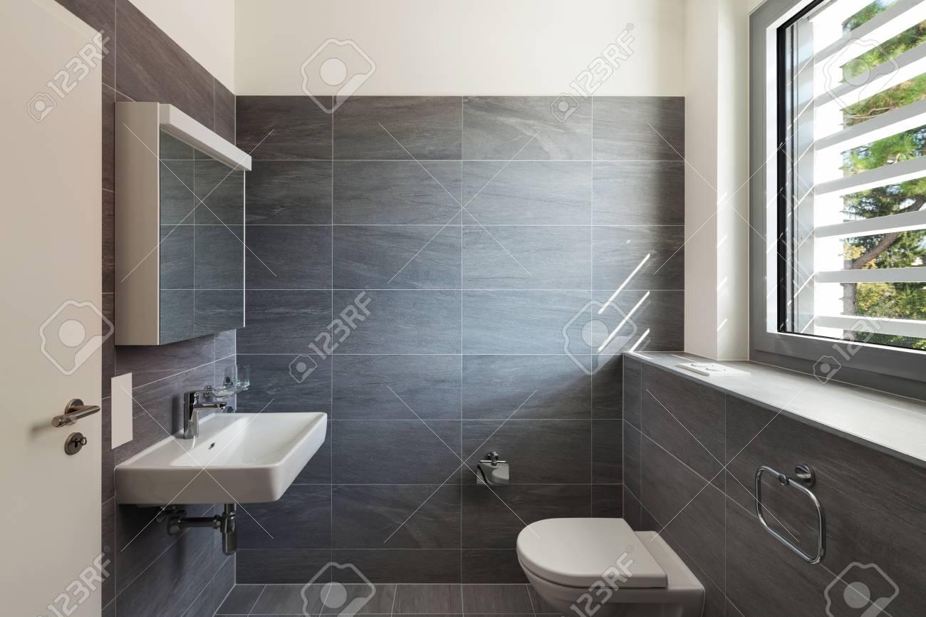Intérieur d\'une maison moderne, salle de bains gris, murs carrelés et  plafond blanc
