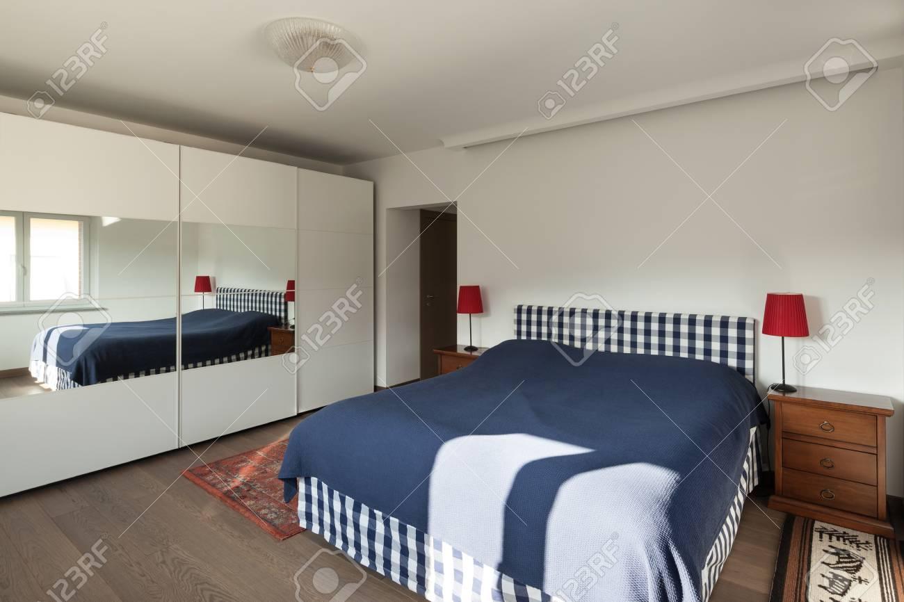 Interni dell\'appartamento, camera da letto con pavimento in legno e pareti  bianche