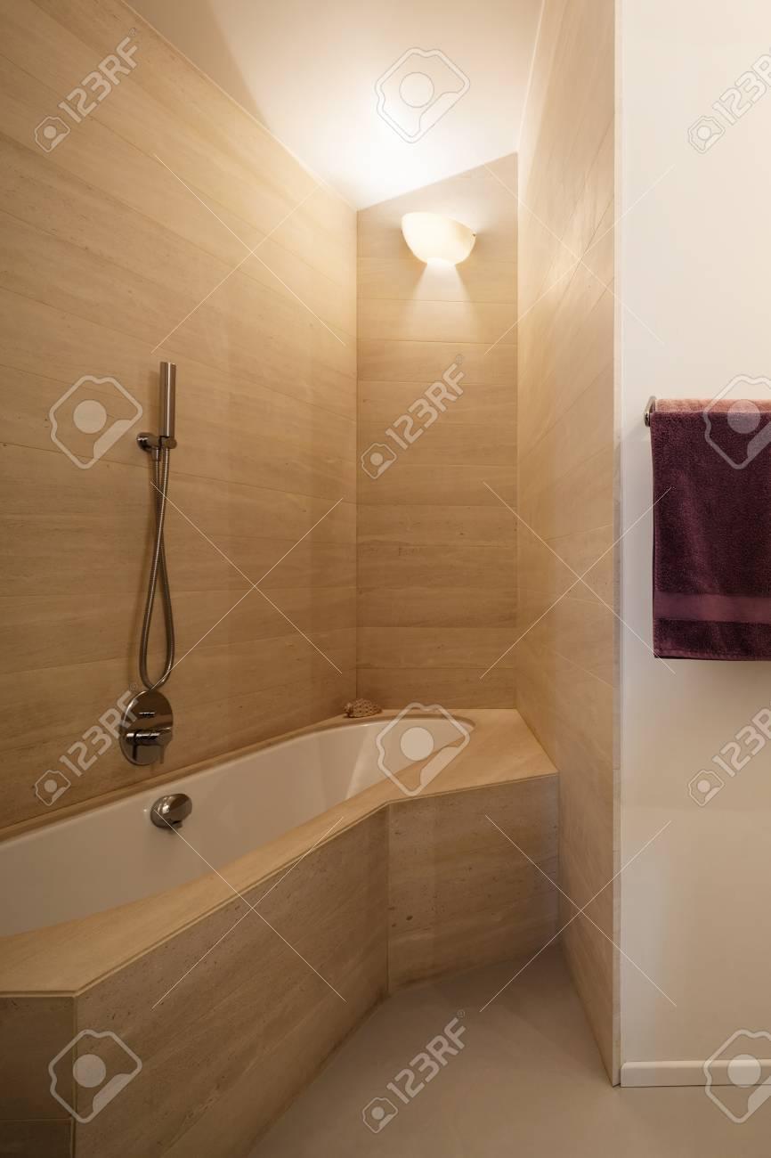 Cuarto de baño moderno, bañera con azulejos de mármol en las paredes.