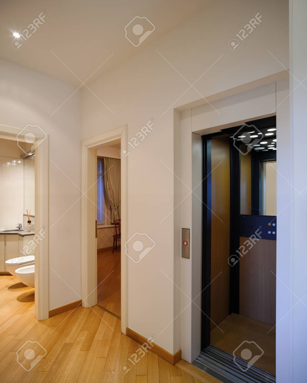 Passageway With Bathroom, Lift And An Empty Room With A Chair Stock ...