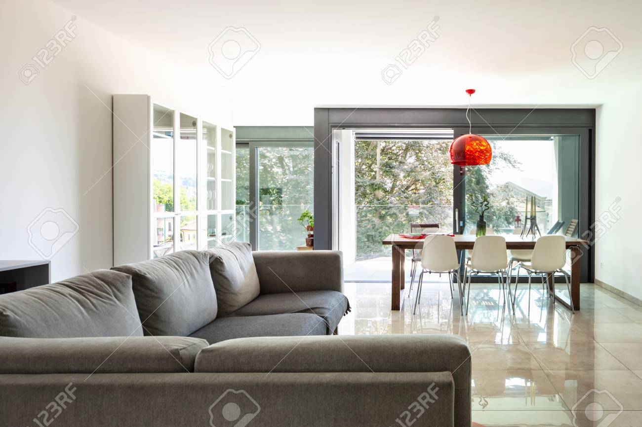 Living room with large designer sofa in modern apartment. Nobody..