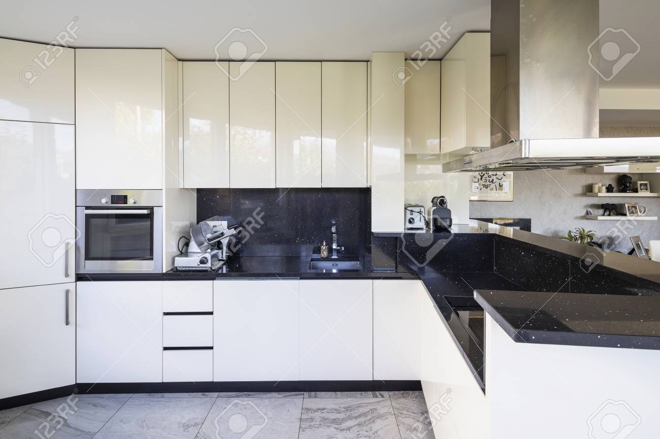 White kitchen with black marble top and large hood. Nobody inside