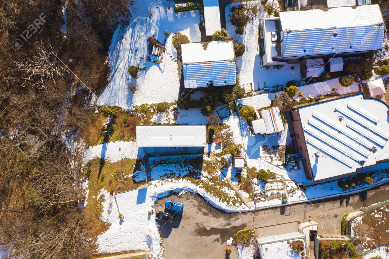 Top view of a house with a snowy roof. Shooting with a drone. - 162260860