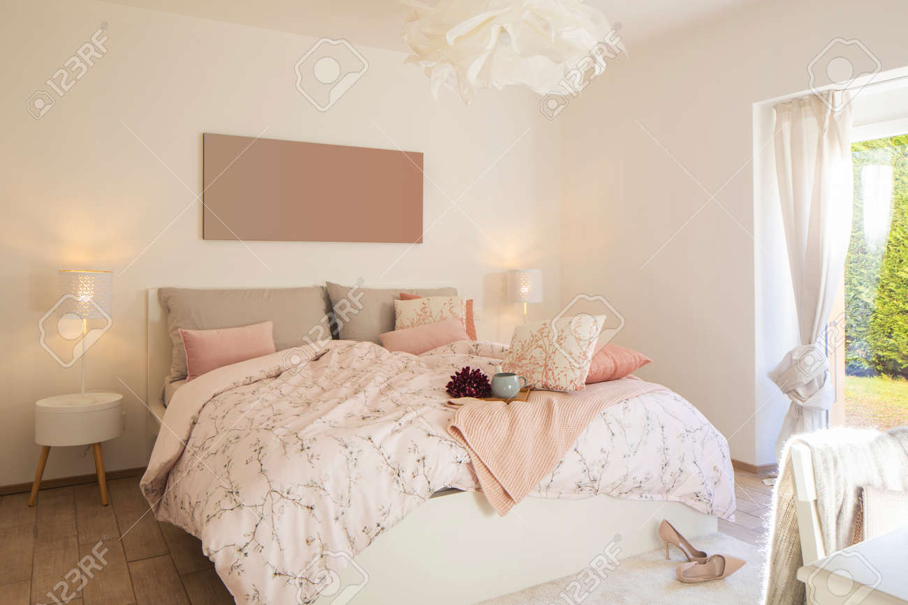 Modern, bright and luxury bedroom in design apartament. Fresh bed sheets and pillows above. There's a tray with a cup for breakfast. - 163075630