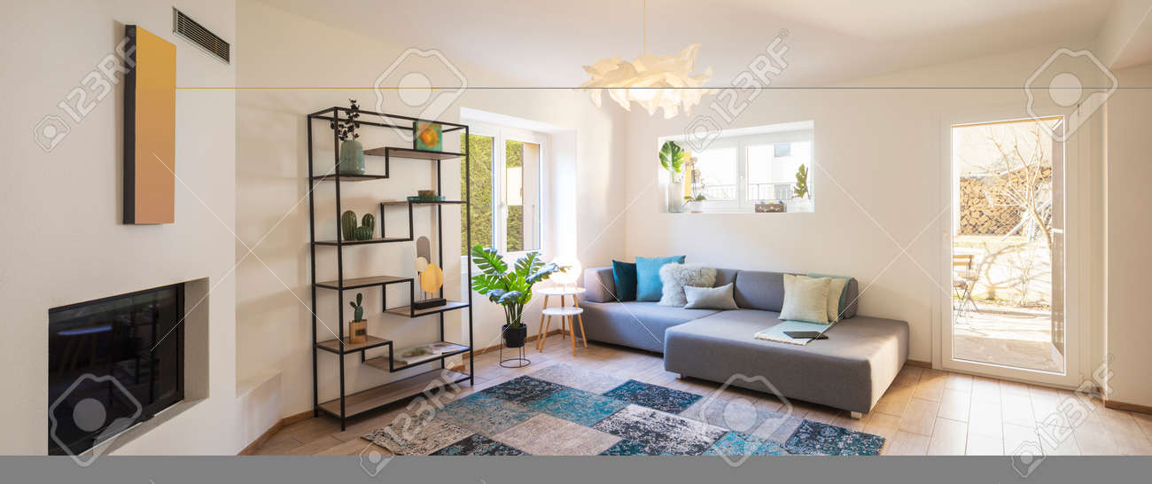 Panorama of wide modern living room with design sofa and large pillows above. Design library and small fireplace. Nobody inside - 163075633